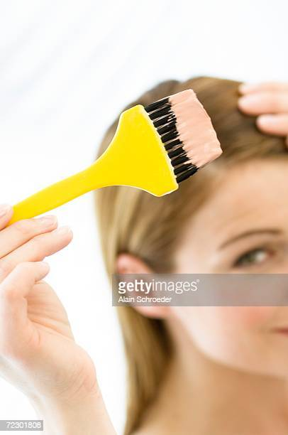 portrait of a young woman dyeing her hair, little brush in her hand - hair colourant stock pictures, royalty-free photos & images