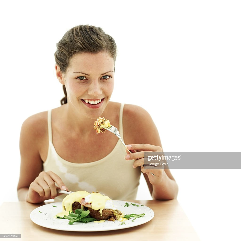 portrait of a young woman eating a meal with a fork : Stock Photo