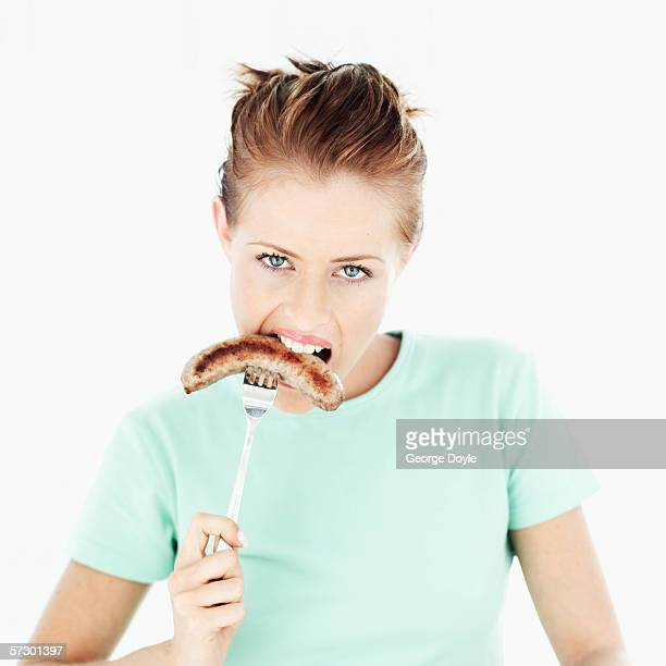 Portrait of a young woman eating a sausage on a fork
