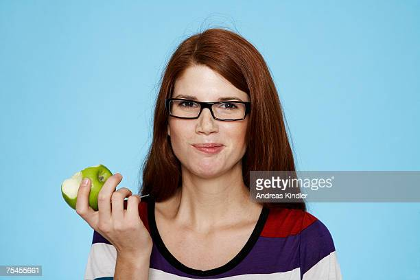 Portrait of a young woman eating an apple.