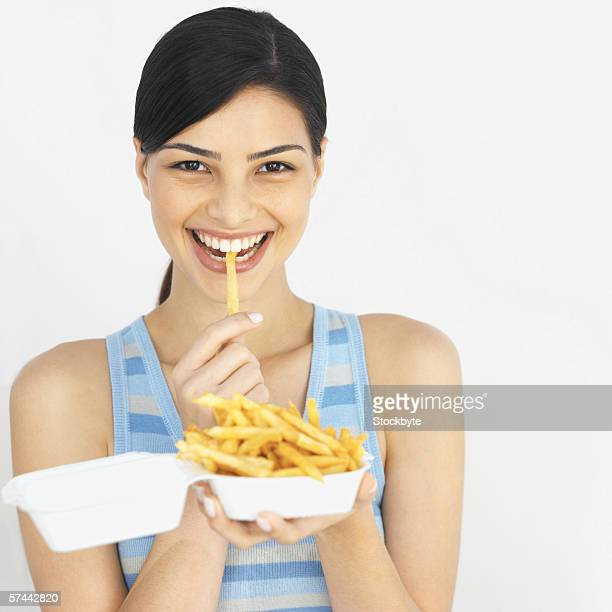 Portrait of a young woman eating fries