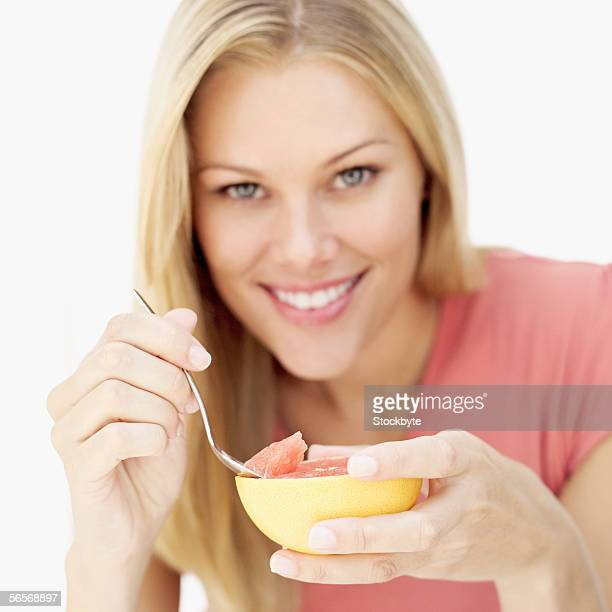portrait of a young woman eating grapefruit with a spoon