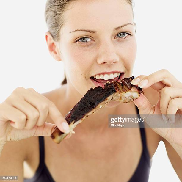 portrait of a young woman eating grilled spare ribs
