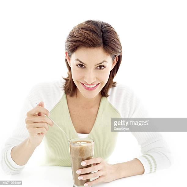 portrait of a young woman eating ice cream from a milkshake