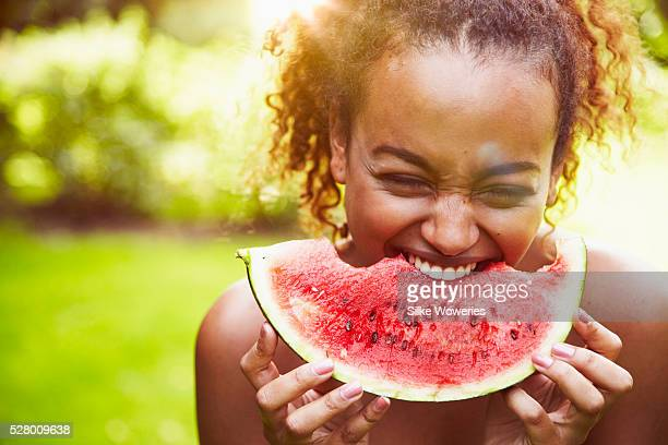 portrait of a young woman eating watermelon on a sunny day, backlit - watermelon stock pictures, royalty-free photos & images