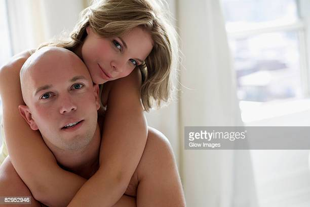 Portrait of a young woman embracing a young man from behind