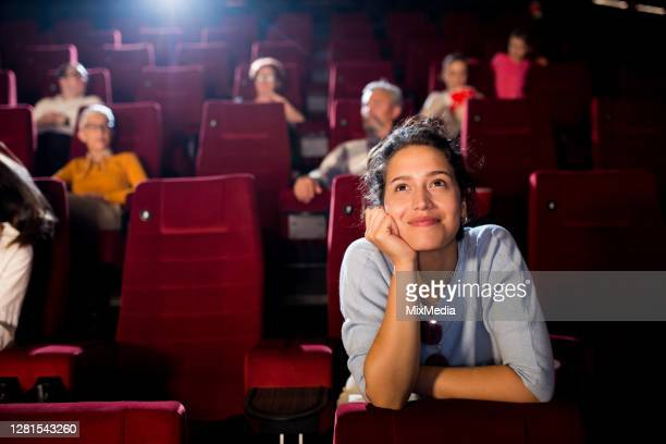 portrait of a young woman enjoying a romantic movie at the cinema - film premiere stock pictures, royalty-free photos & images