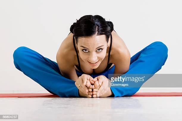 portrait of a young woman exercising on an exercising mat - beautiful women bent over stock photos and pictures