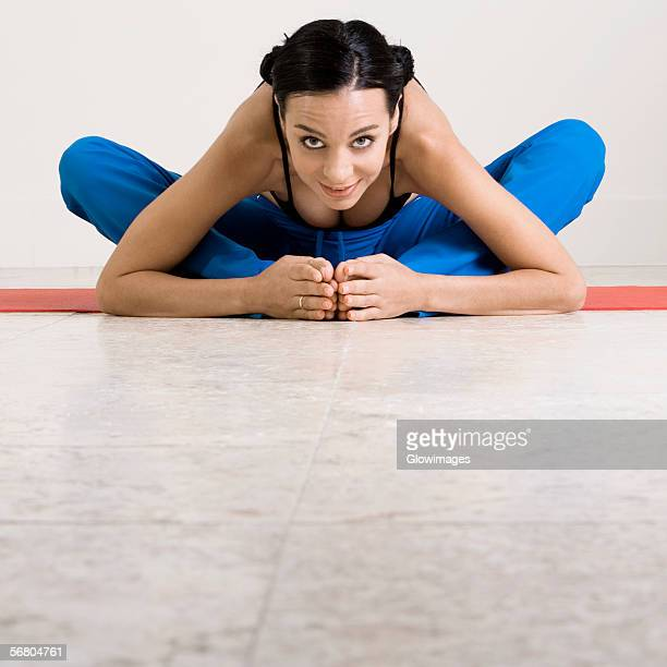 portrait of a young woman exercising on an exercising mat - bend over cleavage stock photos and pictures