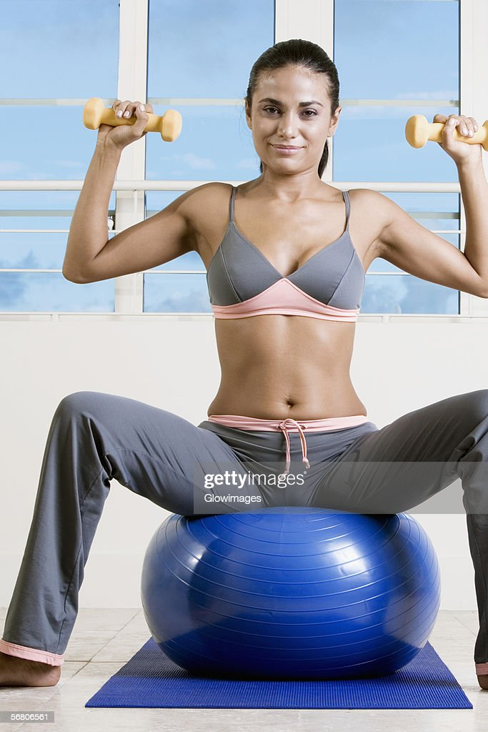 Portrait Of A Young Woman Exercising With Dumbbells On A