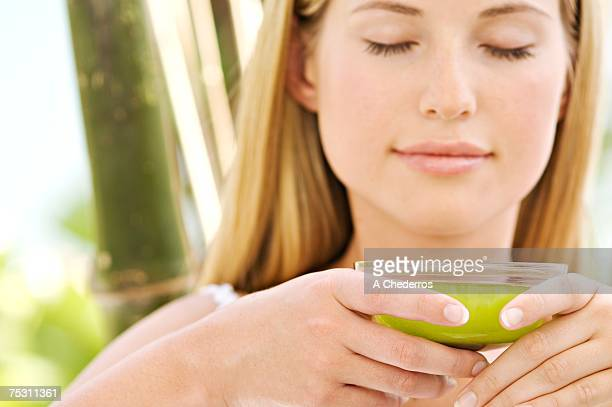 Portrait of a young woman, eyes shut, holding a green tea cup, outdoors
