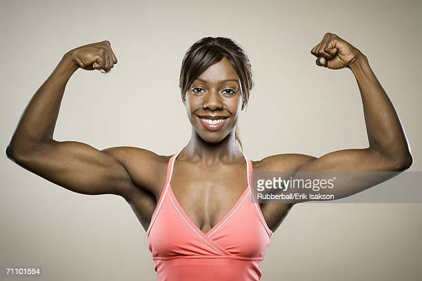 portrait of a young woman flexing her muscles - black female bodybuilder stock photos and pictures