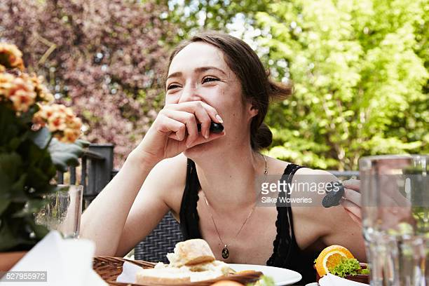 portrait of a young woman fooling around at table eating grapes - solo ragazze foto e immagini stock
