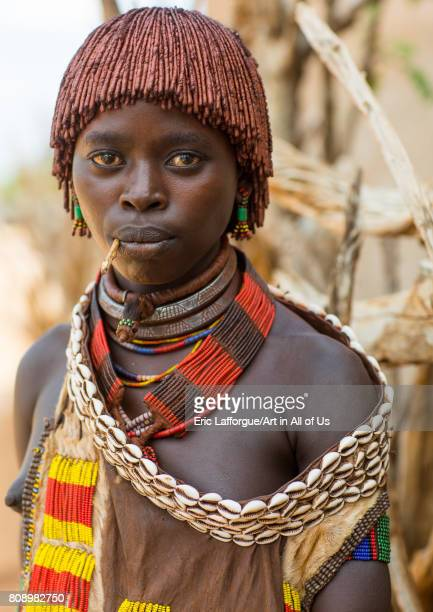 Portrait of a young woman from Hamer tribe with a beaded necklaces and cauris belt Omo valley Turmi Ethiopia on June 5 2017 in Turmi Ethiopia
