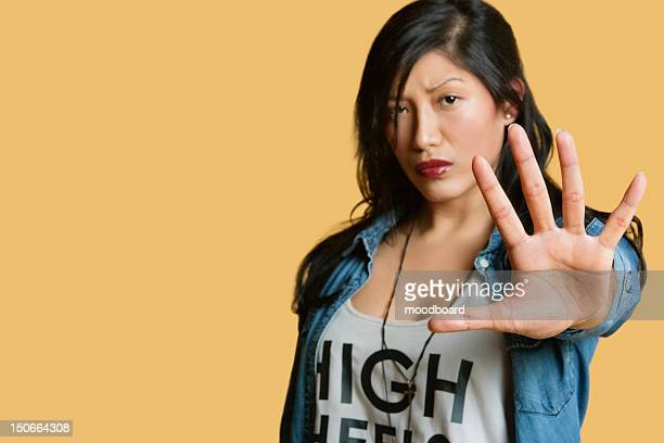 Portrait of a young woman gesturing stop sign over colored background