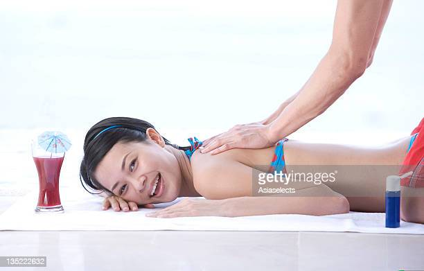 portrait of a young woman getting back massage from a man, phuket, thailand - husband massage wife stock photos and pictures