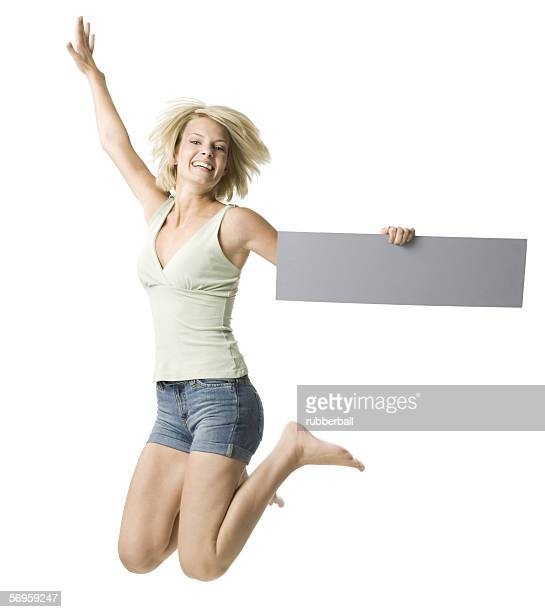 Portrait of a young woman holding a blank sign and jumping