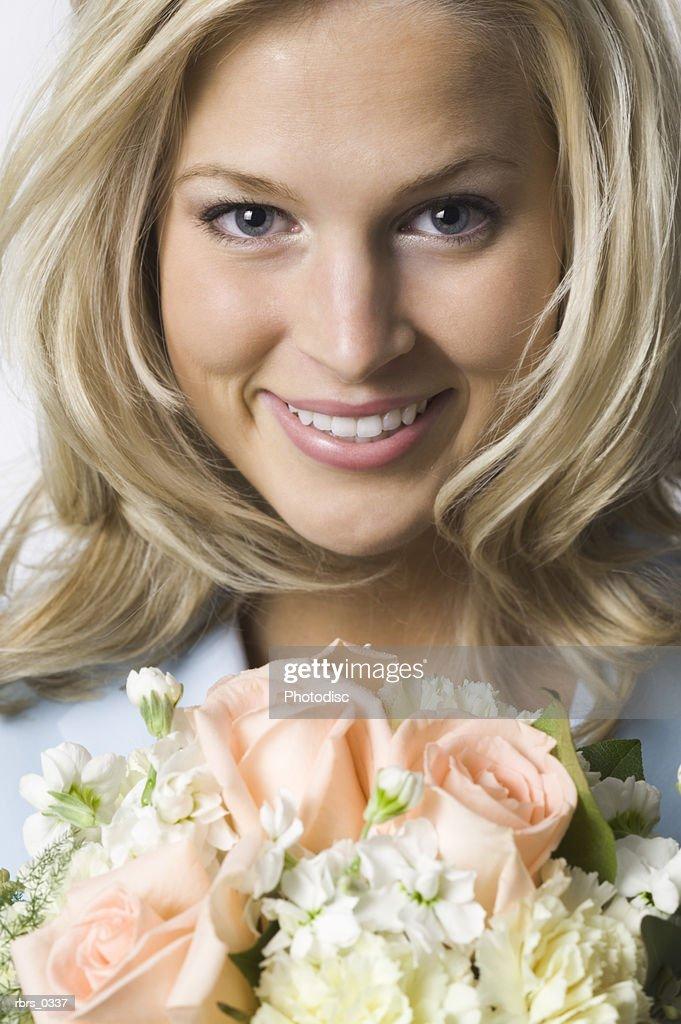 Portrait of a young woman holding a bouquet of flowers : Foto de stock