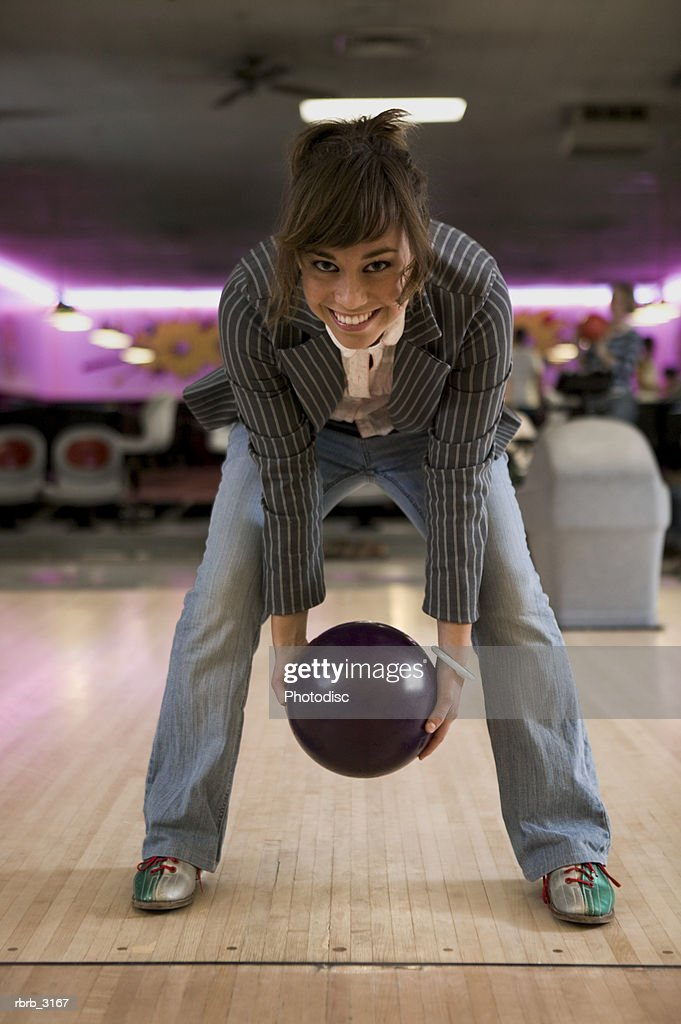 Portrait of a young woman holding a bowling ball at a bowling alley : Foto de stock