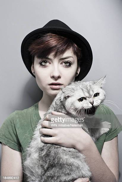 Portrait of a young woman holding a cat