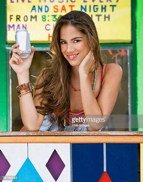 Portrait of a young woman holding a cola can and leaning on a railing