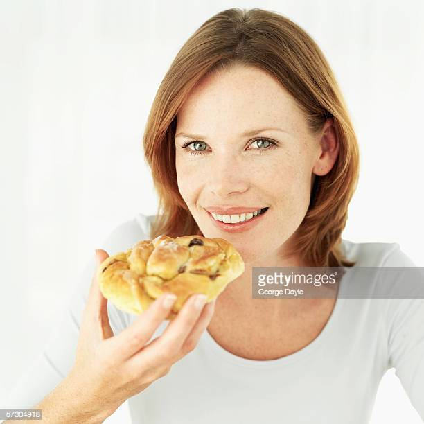 Portrait of a young woman holding a Danish pastry