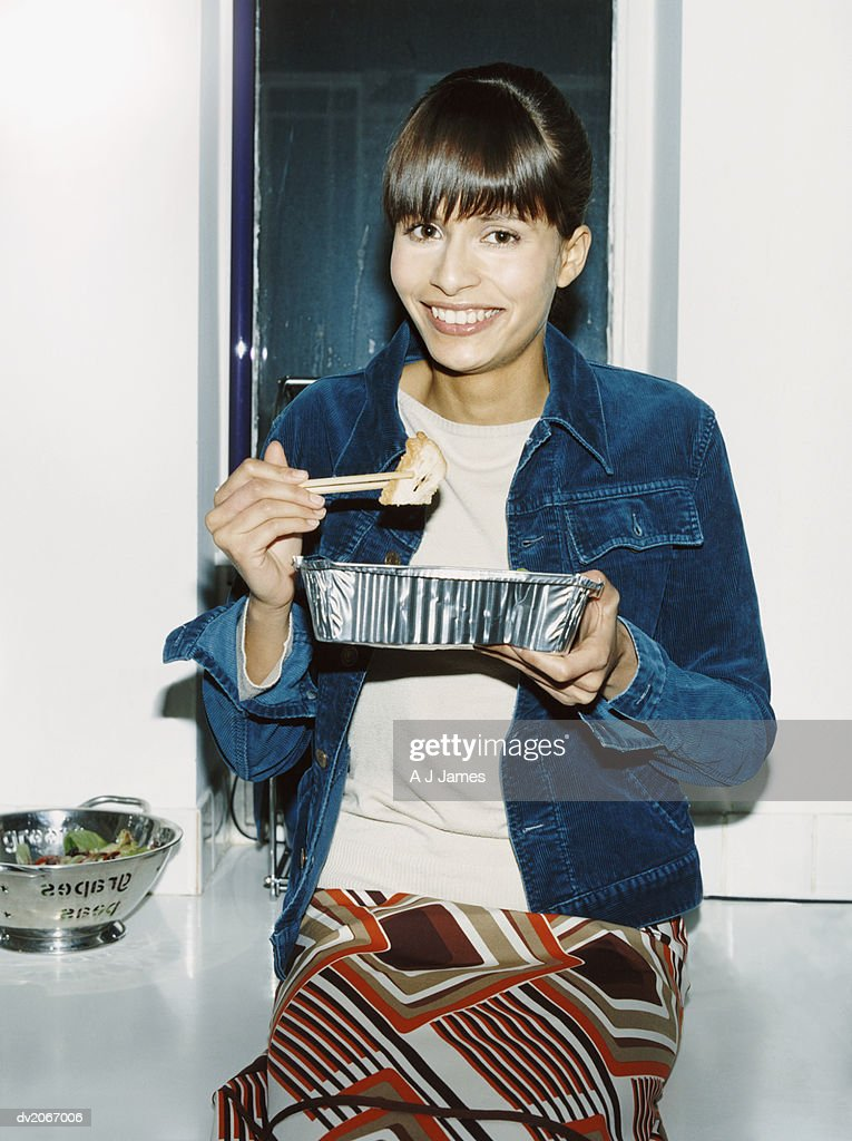 Portrait of a Young Woman Holding a Disposable Fast Food Container and Chopsticks : Stock Photo