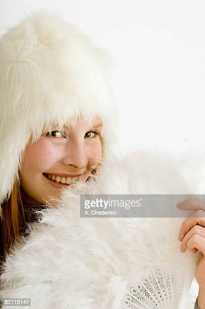 portrait of a young woman holding a feather fan and smiling - feather fan stock-fotos und bilder