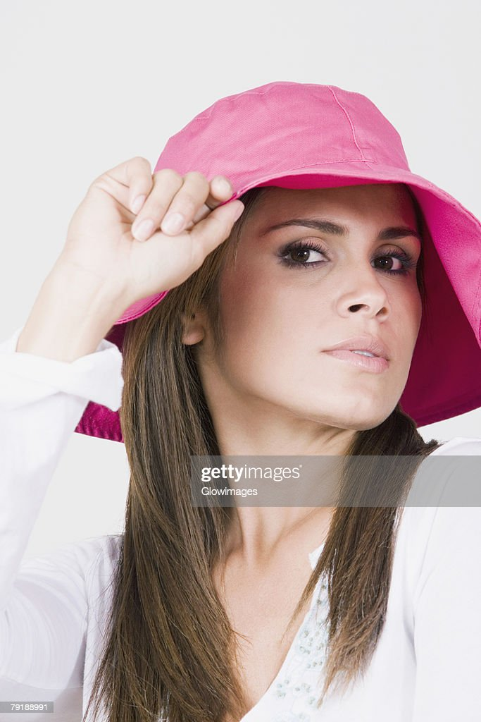 Portrait of a young woman holding a hat : Stock Photo