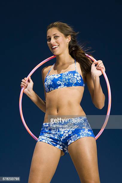 portrait of a young woman holding a hula hoop and smiling - vitalität stock pictures, royalty-free photos & images
