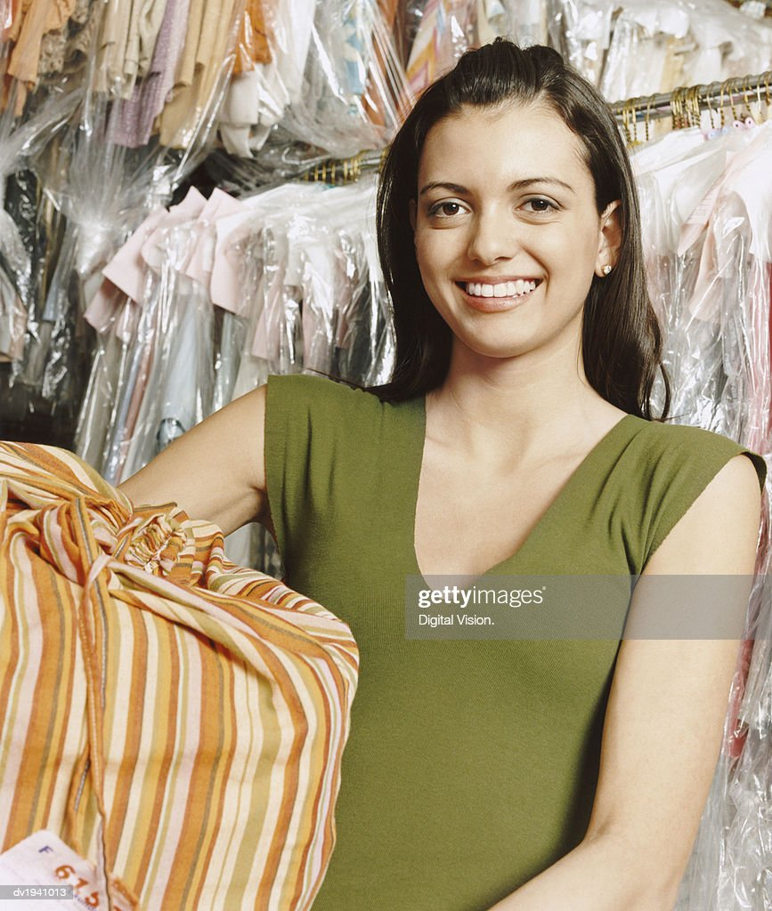 Portrait of a Young Woman Holding a Laundry Bag in a Dry Cleaners : Stock Photo