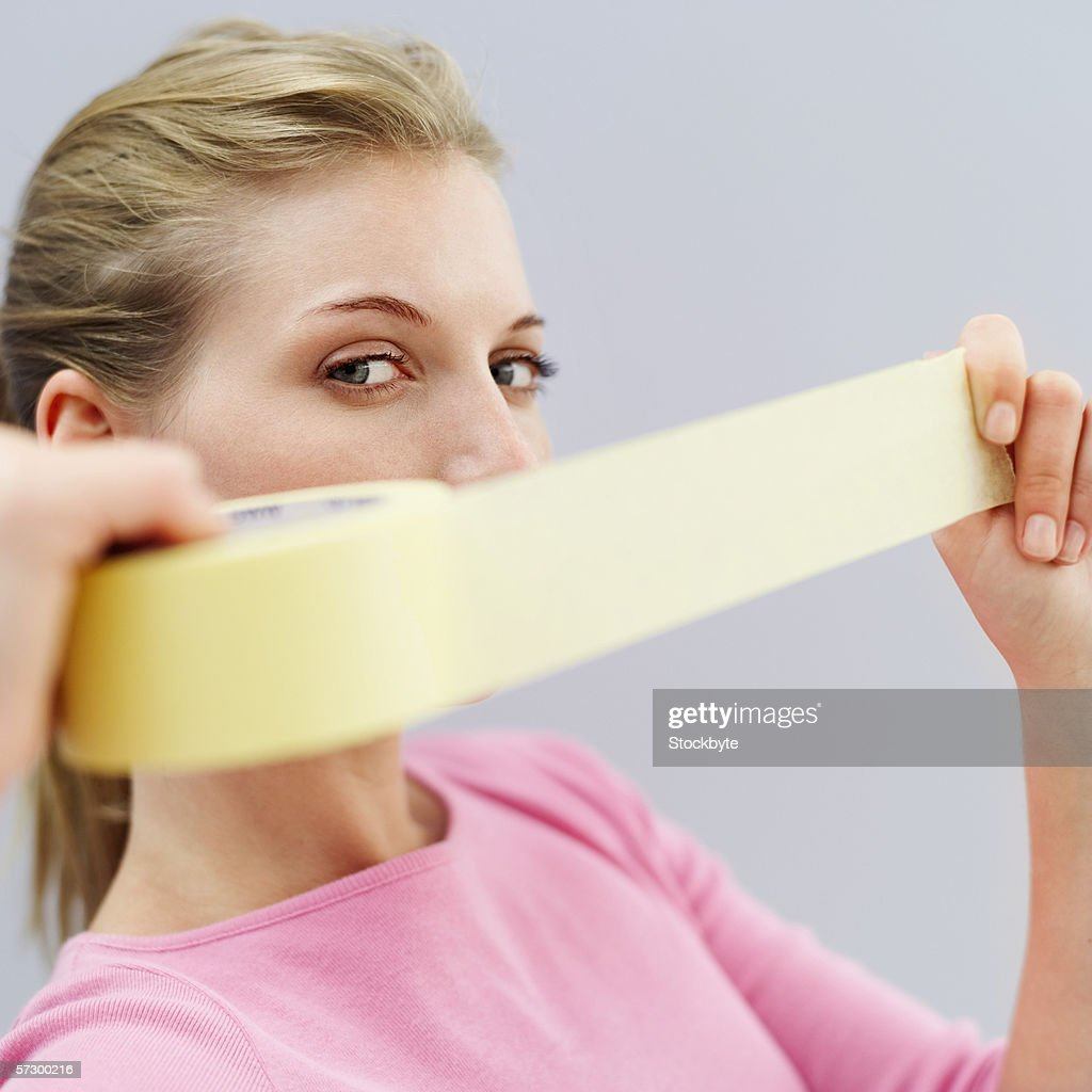 Portrait of a young woman holding a length of masking tape : Stock Photo