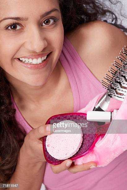 Portrait of a young woman holding a makeup bag