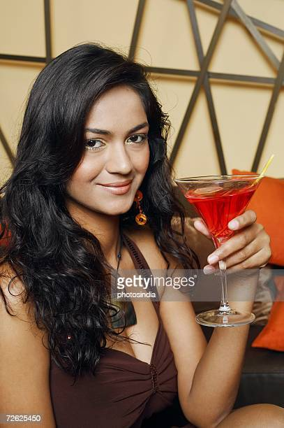 Portrait Of A Young Woman Holding A Martini Glass And Smiling