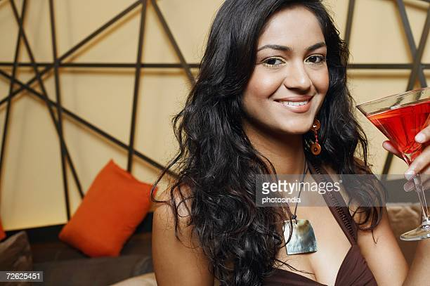 portrait of a young woman holding a martini glass and smiling - indian cleavage stock pictures, royalty-free photos & images
