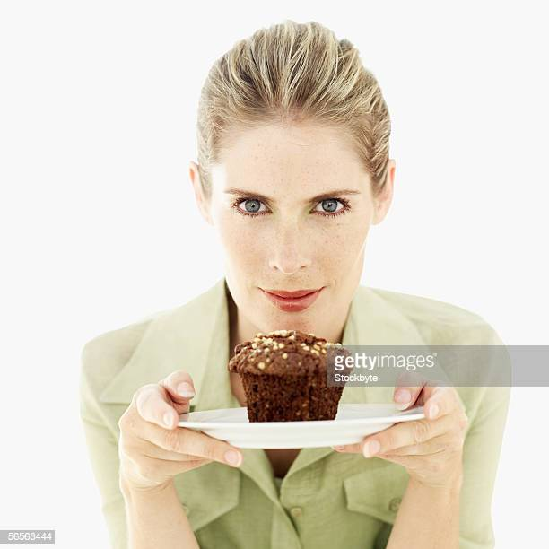 portrait of a young woman holding a muffin on a plate