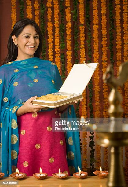portrait of a young woman holding a packet of sweets and smiling - salwar kameez stock pictures, royalty-free photos & images