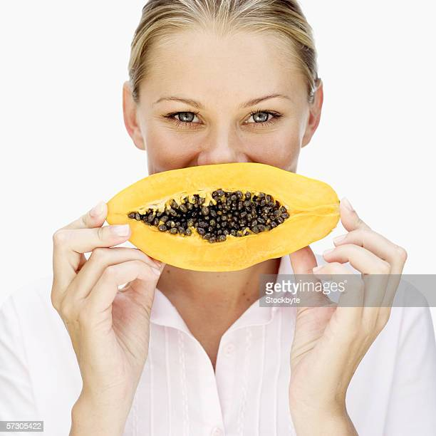 Portrait of a young woman holding a sliced papaya