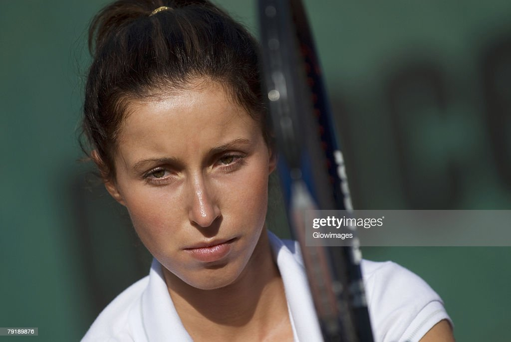 Portrait of a young woman holding a tennis racket : Foto de stock
