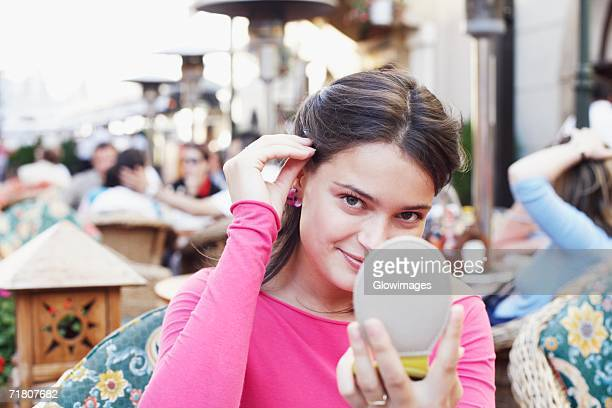 portrait of a young woman holding a vanity mirror - hair part stock pictures, royalty-free photos & images