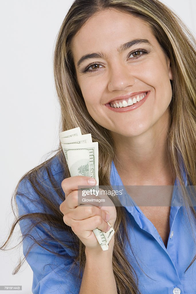 Portrait of a young woman holding American paper currency and smiling : Foto de stock