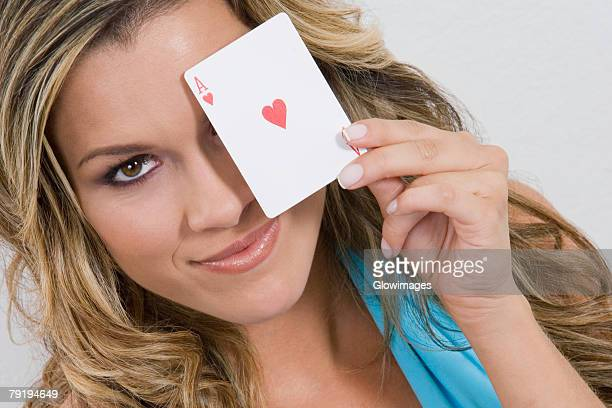 Portrait of a young woman holding an ace card and smiling