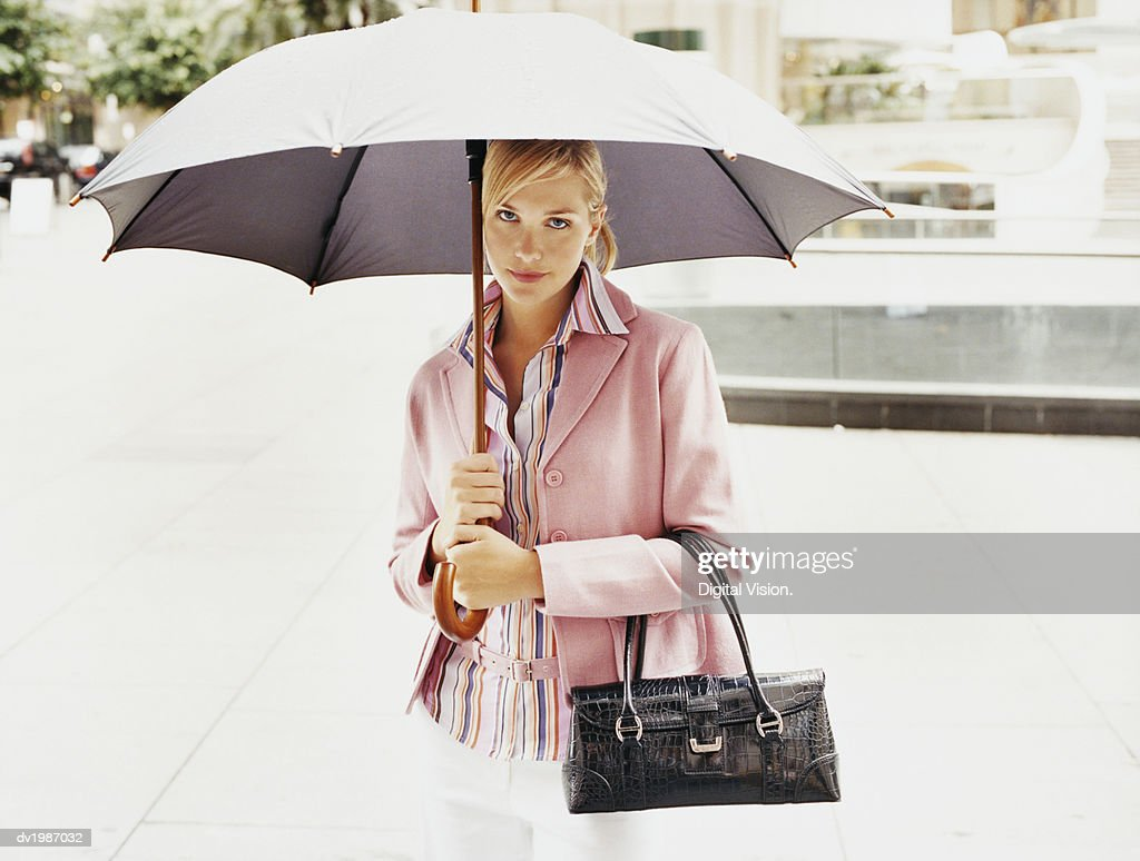 Portrait of a Young Woman Holding an Umbrella in the City : Stock Photo