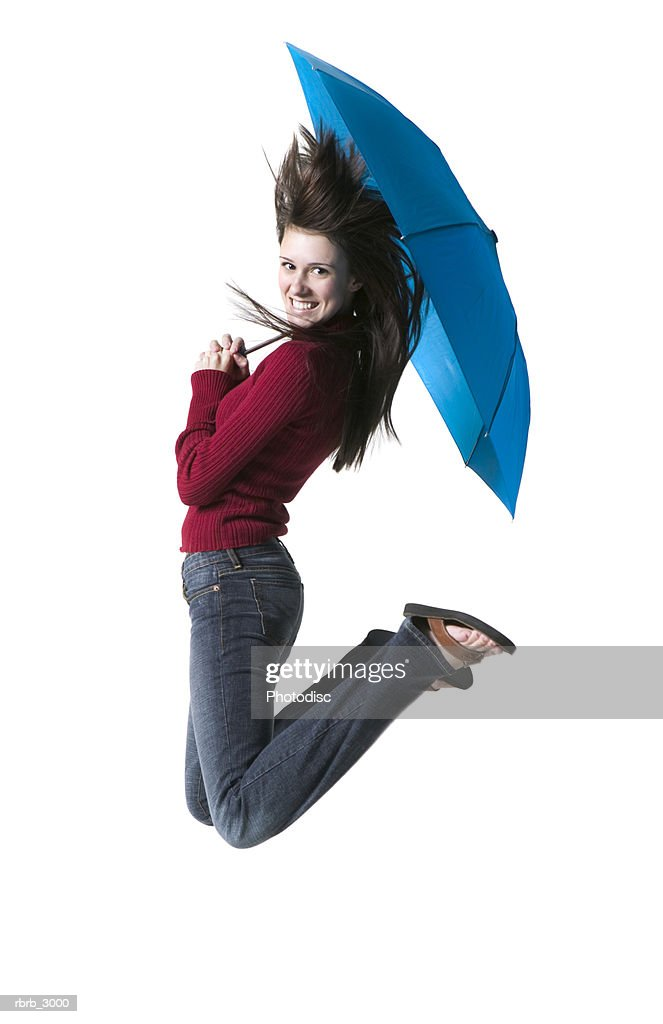 Portrait of a young woman holding an umbrella jumping : Foto de stock