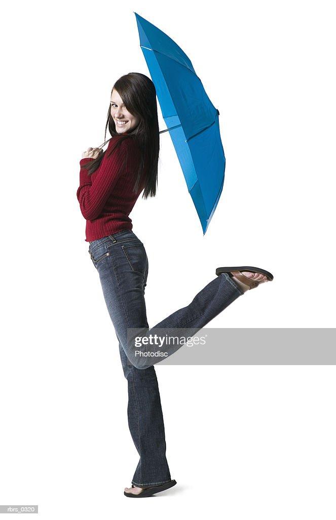 Portrait of a young woman holding an umbrella : Foto de stock