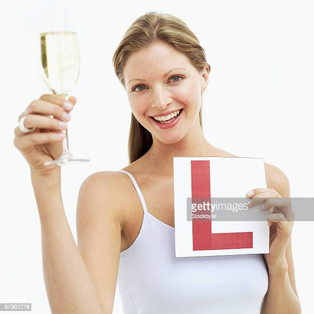 Portrait of a young woman holding glass of champagne and an l-plate
