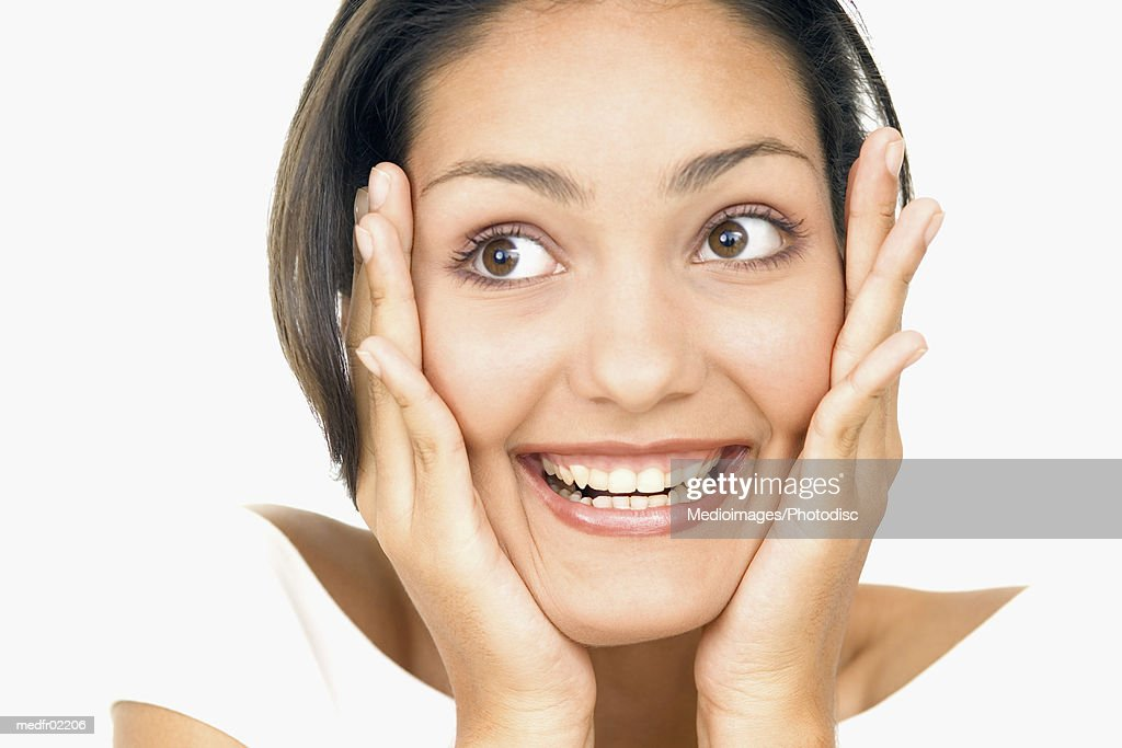 Portrait of a young woman holding her face in surprise : Stock Photo