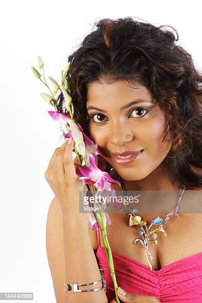 a portrait of a young woman holding orchids - indian cleavage stock pictures, royalty-free photos & images