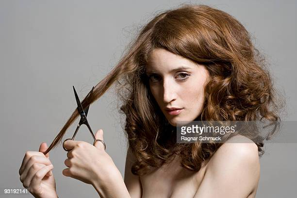 Portrait of a young woman holding scissors to her hair