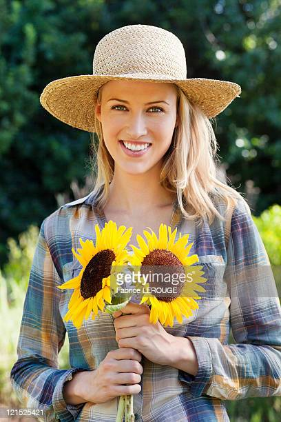 Portrait of a young woman holding sunflowers in a field